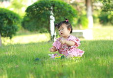 Innocent baby girl play a ball on the lawn. Carefree Chinese little baby girl, sit on a lawn, play with leaves, enjoy free time, embrace nature, beautiful summer Royalty Free Stock Photography