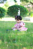 Innocent baby girl play a ball on the lawn. Carefree Chinese little baby girl, sit on a lawn, play with leaves, enjoy free time, embrace nature, beautiful summer Royalty Free Stock Image