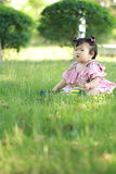 Innocent baby girl play a ball on the lawn. Carefree Chinese little baby girl, sit on a lawn, play with leaves, enjoy free time, embrace nature, beautiful summer Royalty Free Stock Images