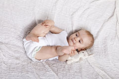 Innocent baby girl playing on the bed Stock Photos
