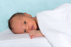 Innocent baby under towel Stock Photos