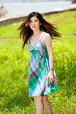 Innocent beautiful asian girl outdoors. Flipping hair and turn with a smile Royalty Free Stock Images