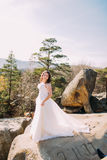 Innocent beautiful bride in luxurious wedding dress. Smiling girl at summer mountain landscape Royalty Free Stock Images