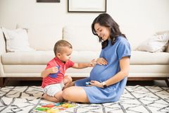 Innocent Boy Touching Abdomen Of Pregnant Mother At Home. Innocent boy touching abdomen of pregnant mother in living room at home Royalty Free Stock Photos