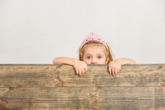 Innocent child peeking over wood border royalty free stock photography