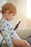 Innocent child playing music on a phone Stock Images