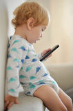 Innocent child playing music on a phone Royalty Free Stock Photos