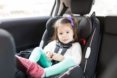 Innocent Child Sitting On Backseat Of Car. Full length portrait of preschool girl sitting on safety seat in car during road trip stock photo