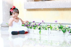 Innocent Chinese baby girl play bubbles in a garden. Cute Asian Chinese baby girl in red bow on her head, wears white dress, play in a garden, innocent little Royalty Free Stock Photo