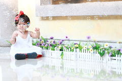 Innocent Chinese baby girl play bubbles in a garden. Cute Asian Chinese baby girl in red bow on her head, wears white dress, play in a garden, innocent little Stock Photos
