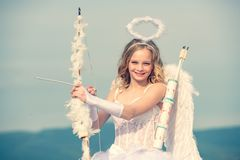 Innocent Girl with angel wings standing with bow and arrow against blue sky and white clouds. St Valentines day. Little stock image