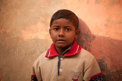 Innocent happy indian poor child. Innocent Smile of indian poor child over wall Stock Image