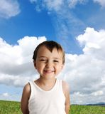 Innocent kid standing on green grass. Meadow Stock Image