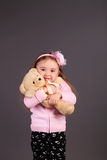 Innocent little girl playing with a bear Royalty Free Stock Photo