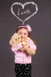 Innocent little girl playing with a bear Stock Images