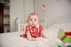 Girl in Red Dress. Innocent little girl in red dress on bed Stock Photography