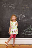 Innocent little girl standing with chalk drawings at home Stock Image