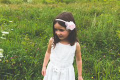 Innocent little girl in white dress outdoors in park with wild grass Stock Images