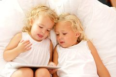 Innocent little sisters using digital tablet on bed. Top view portrait of innocent little girls lying together on bed and using digital tablet royalty free stock photo
