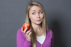 Innocent 20s girl holding an appetizing apple with desire Stock Photos