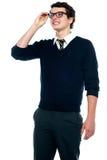 Innocent schoolboy adjusting his eyeglasses Royalty Free Stock Image