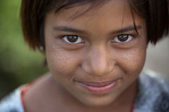 Innocent smile of indian female child. Poor, dirty, rough skin but bright eyes Royalty Free Stock Photography