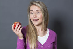 Innocent smiling 20s girl holding appetizing apple with desire Royalty Free Stock Photography