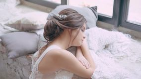 Innocent sweet girl in a long white luxury dress, dark hair in a neat hairdo, looking thoughtfully at a large window. Comfortably lying on a soft window-sill stock video footage