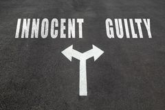 Innocent vs guilty choice concept. Two direction arrows on asphalt Stock Image