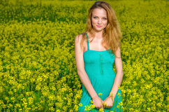 Innocent woman on the yellow field. Innocent Portrait of a beautiful blonde in posing in oilseed Rape Stock Photos