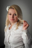 Innocently mischievous. Blond woman in white playing with her hair smiling mischievous Royalty Free Stock Photos