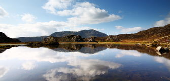 Innominate Tarn near Haystacks. Clouds and fells reflect in the waters of Innominate Tarn, near Haystacks. Alfred Wainwrights ashes are scattered here Stock Photos