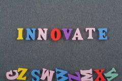 INNOVA la palabra en el fondo negro del tablero compuesto de letras de madera del ABC del bloque colorido del alfabeto, copia el  Fotos de archivo