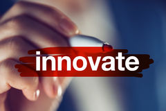 Innovate business concept. Businesswoman highlighting word with red marker pen stock image