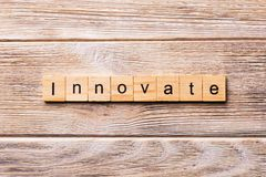 INNOVATE word written on wood block. INNOVATE text on wooden table for your desing, concept.  stock photography
