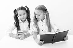 Innovatie en archaïsmeconcept Kinderen gelezen document boek en elektronisch mobiel apparaat die innovatie en archaïsme gebruiken stock fotografie