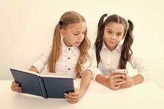 Innovatie en archa?smeconcept Kinderen gelezen document boek en elektronisch mobiel apparaat die innovatie en archa?sme gebruiken royalty-vrije stock afbeeldingen