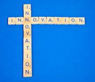 Innovation. Wooden letter blocks isolated on blue background stock images