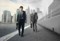 Innovation. Young businessman and older pale businessman walking on a city street Stock Photos