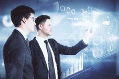 Innovation and analytics. Handsome businessmen drawing abstract digital business hologram on blurry background. Innovation and analytics concept. 3D Rendering royalty free stock images