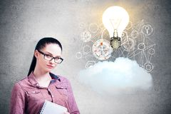 Innovation concept. Attractive businesswoman with abstract glowing lamp, business hologram and cloud on concrete background. Innovation concept Royalty Free Stock Images