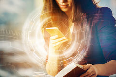 Innovation concept. Attractive young woman using smartphone and holding open book on blurry background with digital business buttons. Innovation concept. Double stock photos