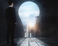 Innovation concept. Side view of penisve young businessman standing in abstract room with light bulb opening, city view and daylight. Innovation concept. 3D Stock Images