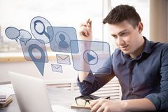 Innovation concept. Side view of young businessman using laptop with abstract media interface at workplace. Innovation concept stock photo