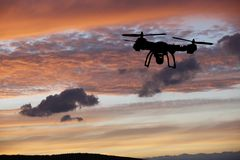 Innovation concept. Silhouette of drone flying on sunset. Heavy lift drone photographing Stock Photos