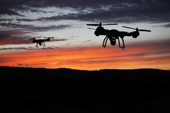 Innovation concept. Silhouette of drone flying on sunset. Heavy lift drone photographing Stock Images