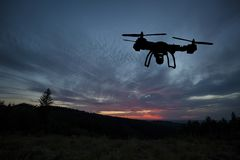 Innovation concept. Silhouette of drone flying on sunset. Heavy lift drone photographing Royalty Free Stock Image