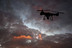 Innovation concept. Silhouette of drone flying on sunset. Heavy lift drone photographing Stock Photography
