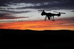 Innovation concept. Silhouette of drone flying on sunset. Heavy lift drone photographing Royalty Free Stock Images