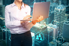 Innovation concept. Unrecognizable woman using laptop on abstract city background with creative digital business projection. Innovation concept. Double exposure Stock Photography